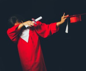 A student dabbing after receiving her diploma.